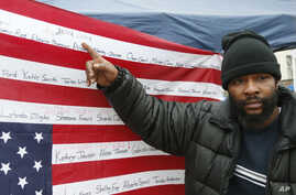 Jamine Clark points to the name of his brother, Jamar Clark, on an upside-down flag bearing names of people killed at the hands of police, outside the Minneapolis Police Department's Fourth Precinct, Nov. 17, 2015, in Minneapolis.