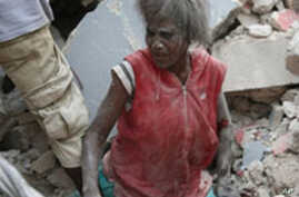 A Haitian woman is helped from the rubble of a damaged building, 12 Jan 2010, in Port-au-Prince after a huge earthquake measuring 7.0 rocked the impoverished Caribbean nation