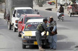 An Afghan policeman searches a passenger at a checkpoint in Kandahar, Afghanistan, Jan. 26, 2016. An Afghan official says that a policeman has turned his weapon on fellow police officers at a checkpoint in the country's south, killing 10 policemen.