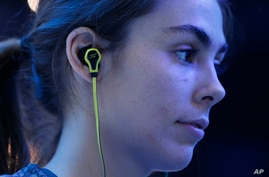 FILE - A young woman is seen wearing headphones at the Consumer Electronics Show in Las Vegas Jan. 6, 2015.