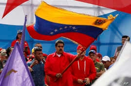 Venezuela's President Nicolas Maduro waves the Venezeulan flag during a rally in Caracas, Venezuela, July 27, 2017. Maduro has provoked international outcry and enraged an opposition demanding his resignation with his push to elect an assembly that w