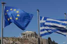 The Greek, right, and the European flags wave under the ancient Acropolis hill in Athens, Sunday, July 5, 2015.
