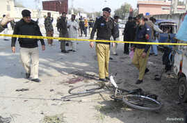 Security officials examine the site of a bomb blast in Kohat, Khyber Pakhtunkhwa province, Pakistan, Feb. 23, 2014.