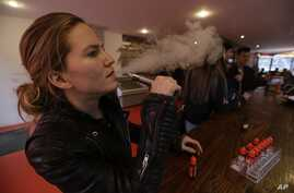 FILE - Talia Eisenberg, co-founder of the Henley Vaporium, uses her vaping device in New York, Feb. 20, 2014.