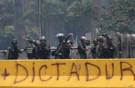 A Venezuelan  National Guard officer throws a tear gas grenade towards demonstrators during a protest in Caracas, Venezuela,  April 10, 2017. Thousands of people in Venezuela's capital are protesting against the government of President Nicolas Maduro