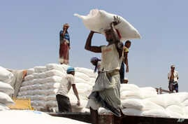 FILE - Men deliver U.N. World Food Programme (WFP) aid in Aslam, Hajjah, Yemen, Sept. 21, 2018.