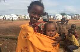 Machi, an Ethiopian refugee in Kenya's Dambala Fachana camp, carries her youngest sister, Lelo. They came to the camp with their family in March. (D. Gelmo/VOA)