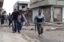 Image made from amateur video purports to show a Syrian rebel helping an injured man in Rastan, Homs, Syria. Syrian troops shelled the rebel-held town, sparking intense clashes that sent bloodied victims flooding into hospitals and clinics, activists