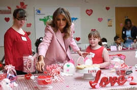 First lady Melania Trump, center, helps to fill candy boxes during a visit to the National Institutes of Health to see children at the Children's Inn in Bethesda, Md., to celebrate Valentine's Day, Feb. 14, 2019.