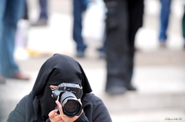 FILE - A burqa-clad female reporter takes photos of protesters at a rally.