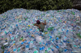 A worker uses a rope to move through a pile of empty plastic bottles at a recycling workshop in Mumbai June 5, 2014.