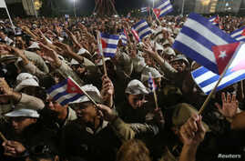 People wave Cuban flags as they attend a massive tribute to Cuba's late former president, Fidel Castro, in Revolution Square in Havana, Cuba, Nov. 29, 2016.