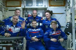 Canadian Space Agency astronaut David Saint-Jacques waves upon uniting with the rest of the crew members on the International Space Station after its capsule hatch opened upon docking in this still image captured from NASA video in space, Dec. 3, 201