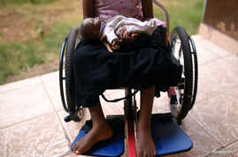 A five-year-old girl poses with her doll as she sits in her wheelchair in the courtyard of the Aberdeen Women's Center, one year after a sexual assault that her family says left her paralyzed, in Freetown, Sierra Leone, Feb. 7, 2019.
