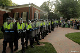 "Virginia State Police officers form a cordon at the University of Virginia ahead of the one year anniversary of the 2017 Charlottesville ""Unite the Right"" protests, in Charlottesville, Va., Aug. 11, 2018."