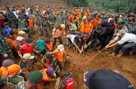 Rescuers try to pull out the body of a victim of a landslide that swept away a village in Jemblung, Central Java, Indonesia, Dec. 14, 2014.