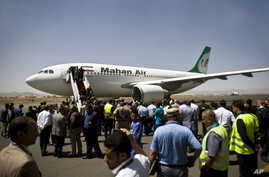 Yemeni airport, security and transportation officials greet a plane from the Iranian private airline, Mahan Air after it lands at the international airport in Sanaa, Yemen, Sunday, March 1, 2015.