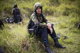 FILE - Juliana, a 20-year-old rebel fighter for the 36th Front of the Revolutionary Armed Forces of Colombia, or FARC, rests from a trek in the northwest Andes of Colombia, in Antioquia state, Jan. 6, 2016. A battle is brewing between Colombia's chie