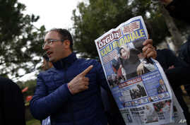 "FILE - A man shows the front page of the daily Ozgur with a headline that reads "" bloody intervention"" as people gather outside the headquarters of Zaman newspaper in Istanbul, March 6, 2016."