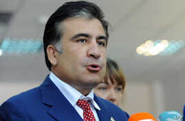 Georgia's President Mikheil Saakashvili speaks to journalists at a polling station in Tbilisi, on October 1, 2012.