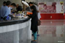 FILE - Customers are seen at a counter inside the Bank Indonesia complex in Jakarta, Indonesia, Dec. 16, 2015.