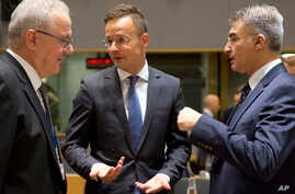 Hungarian Foreign Minister Peter Szijjarto, center, speaks with Malta's Foreign Minister Carmelo Abela, right, and European Commissioner for International Cooperation Neven Mimica during a meeting of EU foreign ministers at the Europa building in Bru