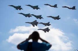 FILE - A man watches Russian military jets performing in Alabino, outside Moscow, Russia, Aug. 12, 2017. Russia's planned 'Zapad 2017' exercises on the border with Baltic states and Poland are viewed with suspicion by NATO alliance members.