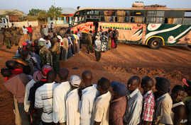 FILE - Passengers hoping to travel to Nairobi line up at a bus in the town of Mandera near the Kenya-Somalia border, Dec. 8, 2014.