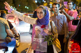 A woman holds a poster of Iranian President Hassan Rouhani during a campaign rally in Tehran, Iran, May 17, 2017.
