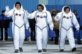 Members of the International Space Station expedition 54/55, Roscosmos cosmonaut Anton Shkaplerov, center, NASA astronaut Scott Tingle, right, and Norishige Kanai, left of the Japan Aerospace Exploration Agency during the send-off ceremony at the Bai...