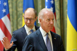 US Vice President Joe Biden (R) and Ukraine's acting Prime Minister Arseniy Yatsenyuk leave after a joint press conference in Kyiv on April 22, 2014.