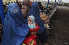 Afghan refugee women sit with their babies as they wait with others to be repatriated to Afghanistan, at the United Nations High Commissioner for Refugees (UNHCR) office on the outskirts of Peshawar, Feb. 2, 2015.