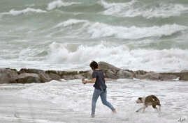 Tropical Weather: A woman runs in the heavy surf with her dog at Sunset Beach in Treasure island, Fla., Monday, June 6, 2016, as Tropical Storm Colin churns in the Gulf of Mexico. Colin was expected to make landfall somewhere along Florida's gulf coa
