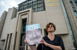 A journalist poses with a portrait of Turkish journalist Ahmet Altan, June 19, 2017, in front of the Istanbul courthouse, where his trial is to take place.