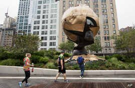Visitors to the World Trade Center stop to look at the Koenig Sphere in Liberty Park, Sept. 6, 2017, in New York.
