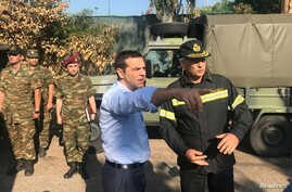 FILE - Greek Prime Minister Alexis Tsipras speaks with a firefighter officer as he visits the village of Mati, following a wildfire near Athens, Greece, July 30, 2018.