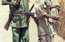 Two Sudanese boy soldiers keep watch outside a rebel military headquarters in remote southern Sudan Feb. 13, 2000.