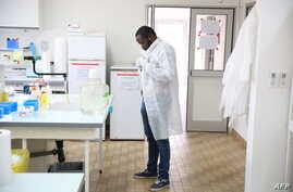 Dr. Mombo dons his white coat as he prepares to analyse samples at the Franceville International Centre of Medical Research (CIRMF) is seen on June 12, 2018 in Franceville.