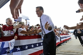 Republican presidential candidate, former Massachusetts Gov. Mitt Romney gestures as he greets supporters as he arrives at a Florida campaign rally at Orlando Sanford International Airport, in Sanford, Fla., Nov. 5, 2012.