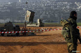 An Israeli soldier stands guard next to an Iron Dome rocket interceptor battery deployed near the northern Israeli city of Haifa, January 28, 2013.