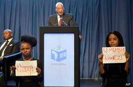 Protesters hold up signs as President Jacob Zuma speaks at the announcement of the results of municipal elections in Pretoria, South Africa, Aug. 6, 2016. The protest refers to Zuma's acquittal for rape in 2006.