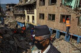 Nepal military personnel and earthquake survivors search for belongings from the rubble of collapsed houses in Sankhu, on the outskirts of Kathmandu, Nepal, May 5, 2015.