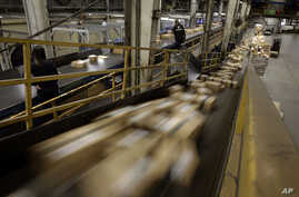 FILE - FedEx Packages move on a conveyor belt at the FedEx hub at Los Angeles International Airport in Los Angeles.