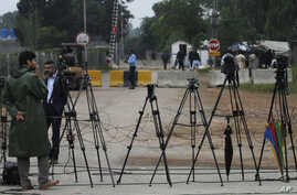 FILE - Pakistani journalists are seen at a stake-out in Islamabad, Pakistan, Nov. 6, 2013. Recently, a Pakistani government body established to regulate private TV channels, has started asserting itself in ways that have raised concerns with media wa
