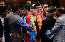 FILE - Nepal's prime minister, Khadga Prasad Oli, center, speaks with members of the cabinet inside the Constituent Assembly in Kathmandu, Nepal, Oct. 11, 2015.