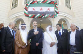 Syrian National Coalition leader Moaz Alkhatib (C) attends the opening of its embassy in Doha, Qatar, Mar. 27, 2013.