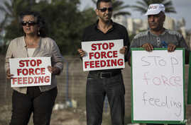 Israeli Arab supporters of Mohammed Allan, a Palestinian prisoner on a hunger strike, hold signs during a support rally outside Barzilai hospital, in the costal city of Ashkelon Israel. Israel passed a law to force feed hunger strikers by a slim marg
