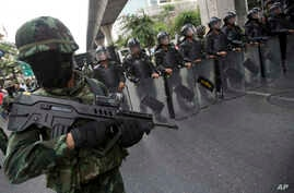 Thai soldiers guard during a protest against the coup in Bangkok, Thailand Saturday, May 24, 2014.