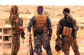 FILE -- A photo provided by the Syrian Democratic Forces (SDF) shows fighters from the SDF looking toward the northern town of Tabqa, Syria, April 30, 2017.