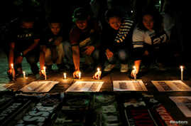 Football supporters from East Java hold a vigil for victims of the suicide bomb attacks in Surabaya at a city park in Jakarta, Indonesia, May 14, 2018.